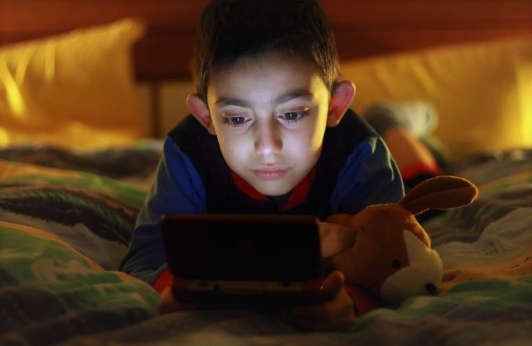 Bigstock image of a kid playing video games on a handheld device