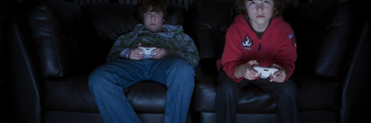 Big stock image of two young men playing video games in the dark